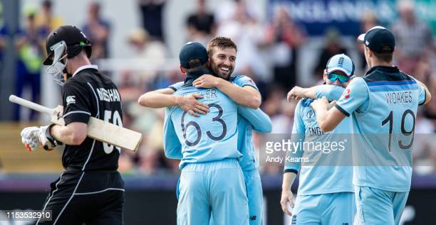 Mark Wood of England celebrates with his team mates after taking the wicket of Jimmy Neesham of New Zealand during the Group Stage match of the ICC...