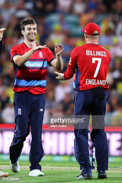 Mark Wood of England celebrates with Sam Billings of England after taking the wicket of Marcus Stoinis of Australia during the Twenty20 International...