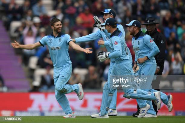 Mark Wood of England celebrates with team mates after dismissing Andre Russell of West Indies during the Group Stage match of the ICC Cricket World...