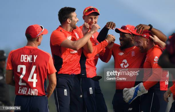 Mark Wood of England celebrates with teammates Joe Denly, Joe Root, Chris Jordan and Jonathan Bairstow after dismissing Carlos Brathwaite of the West...