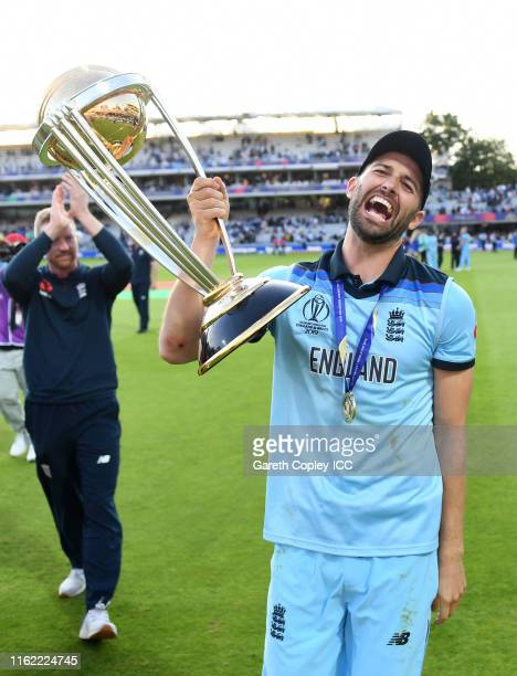 Mark Wood of England celebrates with the trophy after winning the Final of the ICC Cricket World Cup 2019 between New Zealand and England at Lord's...