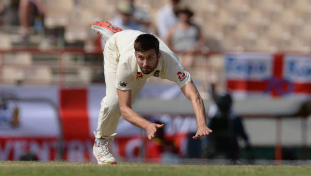 Mark Wood of England tumbles after bowling during the second day of the third test match between the West Indies and England at the Darren Sammy...