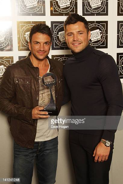 Mark Wright poses with Peter Andre after presenting himn with the Digital TV Personality Award in front of the winners boards at the TRIC Television...