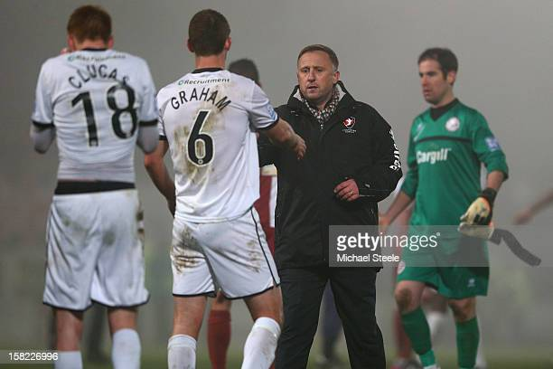 Mark Yates manager of Cheltenham Town shakes hands with Luke Graham of Hereford United after his sides 21 extra time victory during the FA Cup with...