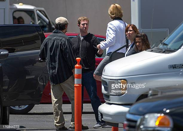 Mark Zuckerberg chief executive officer and founder of Facebook Inc center speaks to an attendee while leaving the company's shareholders meeting in...