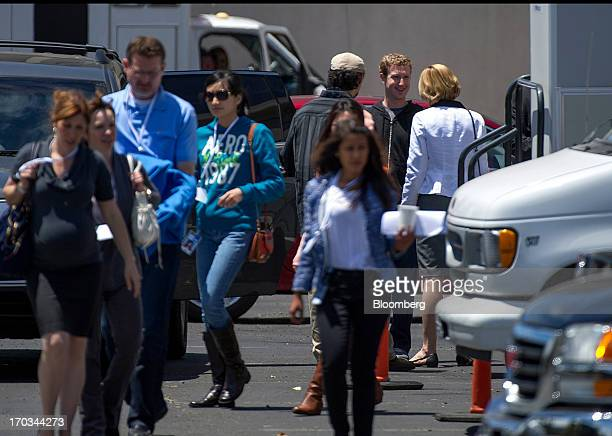 Mark Zuckerberg chief executive officer and founder of Facebook Inc back center speaks to an attendee while leaving the company's shareholders...