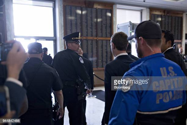 Mark Zuckerberg chief executive officer and founder of Facebook Inc center right walks through the Rayburn House Office building after a House Energy...