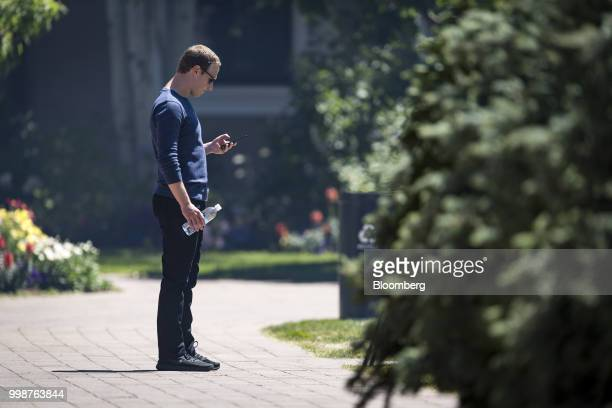 Mark Zuckerberg chief executive officer and founder of Facebook Inc looks at his phone after the morning session at the Allen Co Media and Technology...
