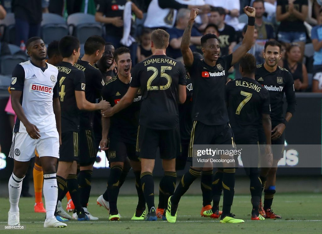 Mark-Anthony Kaye #14 of Los Angeles FC raises his arms in celebration after assisting on a goal by teammate Adama Diomande #99 as Mark McKenzie #4 of Philadelphia Union looks on during the first half during the MLS match at Banc of California Stadium on June 30, 2018 in Los Angeles, California.
