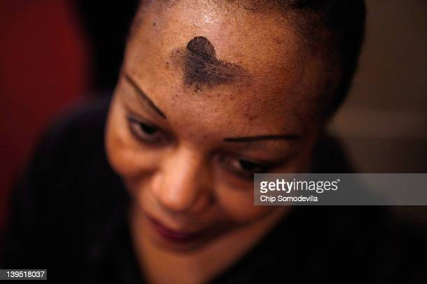 Marked with a cross of black ash on her forehead a Catholics woman prays during an Ash Wednesday Mass at the Cathedral of St Matthew the Apostle...