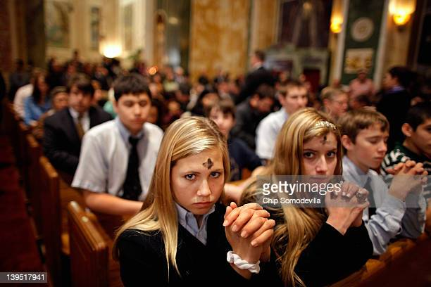 Marked with a cross of black ash on the forehead, Catholics pray during an Ash Wednesday Mass at the Cathedral of St. Matthew the Apostle February...