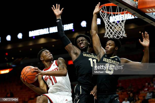 Markell Johnson of the North Carolina State Wolfpack attempts a layup against Simisola Shittu and Clevon Brown of the Vanderbilt Commodores during...