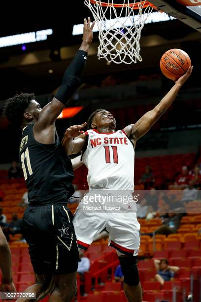 Markell Johnson of the North Carolina State Wolfpack attempts a layup against Simisola Shittu of the Vanderbilt Commodores during the HoopHall Miami...