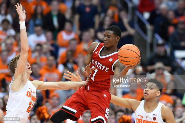 Markell Johnson of the North Carolina State Wolfpack passes the ball between the defense of Marek Dolezaj and Matthew Moyer of the Syracuse Orange...