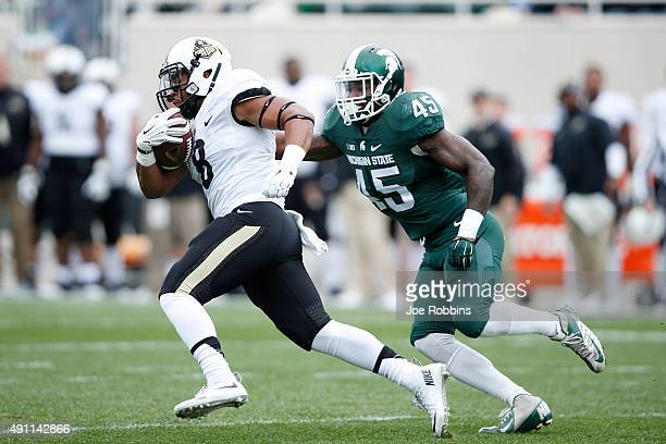 Markell Jones of the Purdue Boilermakers runs the ball against Darien Harris of the Michigan State Spartans in the first quarter at Spartan Stadium...
