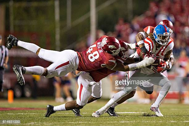 Markell Pack of the Mississippi Rebels is tackled by Deatrich Wise Jr. #48 and Josh Liddell of the Arkansas Razorbacks at Razorback Stadium on...