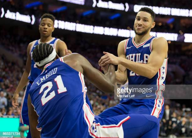 Markelle Fultz and Ben Simmons of the Philadelphia 76ers help up Joel Embiid against the Boston Celtics at the Wells Fargo Center on October 20 2017...