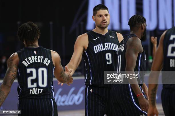 Markelle Fultz and Nikola Vucevic of the Orlando Magic hifive during the game against the Milwaukee Bucks during Round One Game Four of the NBA...