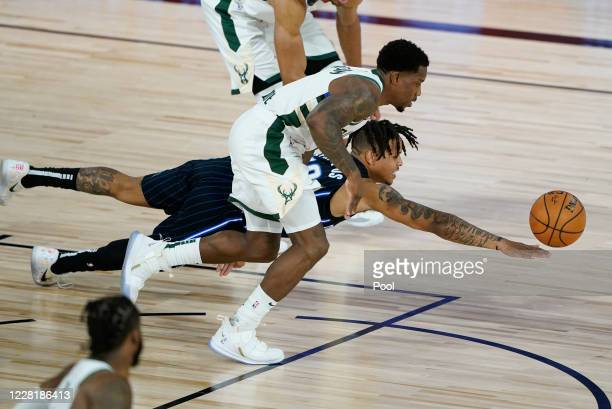 Markelle Fultz of the Orlando Magic dives for a loose ball ahead of Eric Bledsoe of the Milwaukee Bucks during the second half of an NBA basketball...