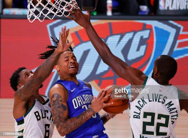Markelle Fultz of the Orlando Magic drives between Eric Bledsoe and Khris Middleton of the Milwaukee Bucks during the third quarter in Game Five of...