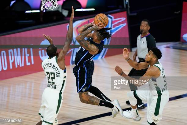 Markelle Fultz of the Orlando Magic drives to the basket between Khris Middleton and Giannis Antetokounmpo of the Milwaukee Bucks during the second...