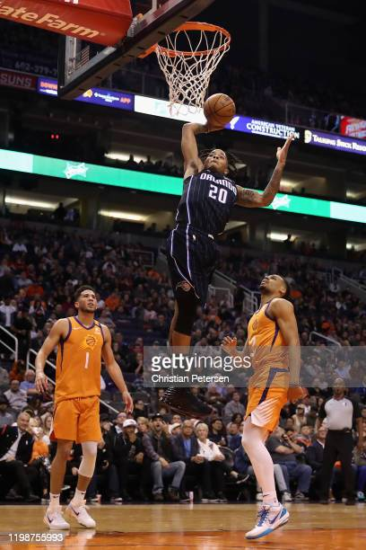 Markelle Fultz of the Orlando Magic goes up for a slam dunk over Devin Booker and Elie Okobo of the Phoenix Suns during the first half of the NBA...