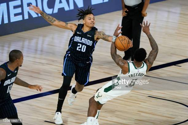 Markelle Fultz of the Orlando Magic tries to block a shot by Eric Bledsoe of the Milwaukee Bucks during the first half of an NBA basketball first...