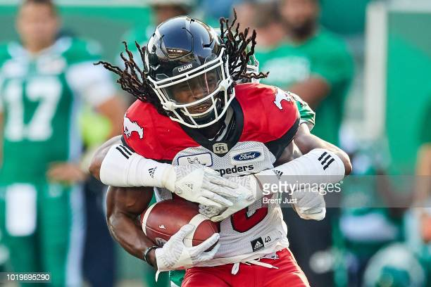 Marken Michel of the Calgary Stampeders is tackled from behind after making a catch in the game between the Calgary Stampeders and Saskatchewan...