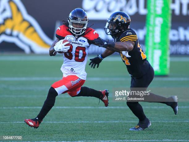 Marken Michel of the Calgary Stampeders tries to break at ackle by Hamilton Tiger-Cats Delvin Breaux during a game at Tim Hortons Field on September...