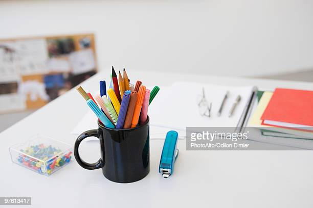 Markers, pens and pencils in mug on desk with school supplies