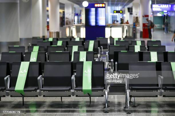 Markers sit on restricted seats for social distancing enforcement as Deutsche Lufthansa AG and airport operator Fraport AG showcase new coronavirus...