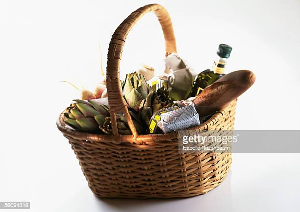 Market basket containing bread, artichokes, and bottle