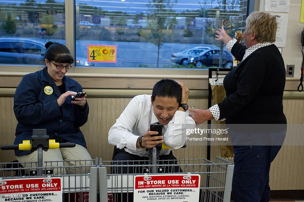 Market Basket employees Lynn Theobald, left, and Edward Foye, check their phones for news after Joanne Twomey, former mayor of Biddeford, ran into the Market Basket store in Biddeford around 7:15 p.m. Friday night, August 22, 2014, to celebrate the indications that Arthur T. Demoulas was going to buy the company. Nothing would be official until the board met to discuss the bids that were made.