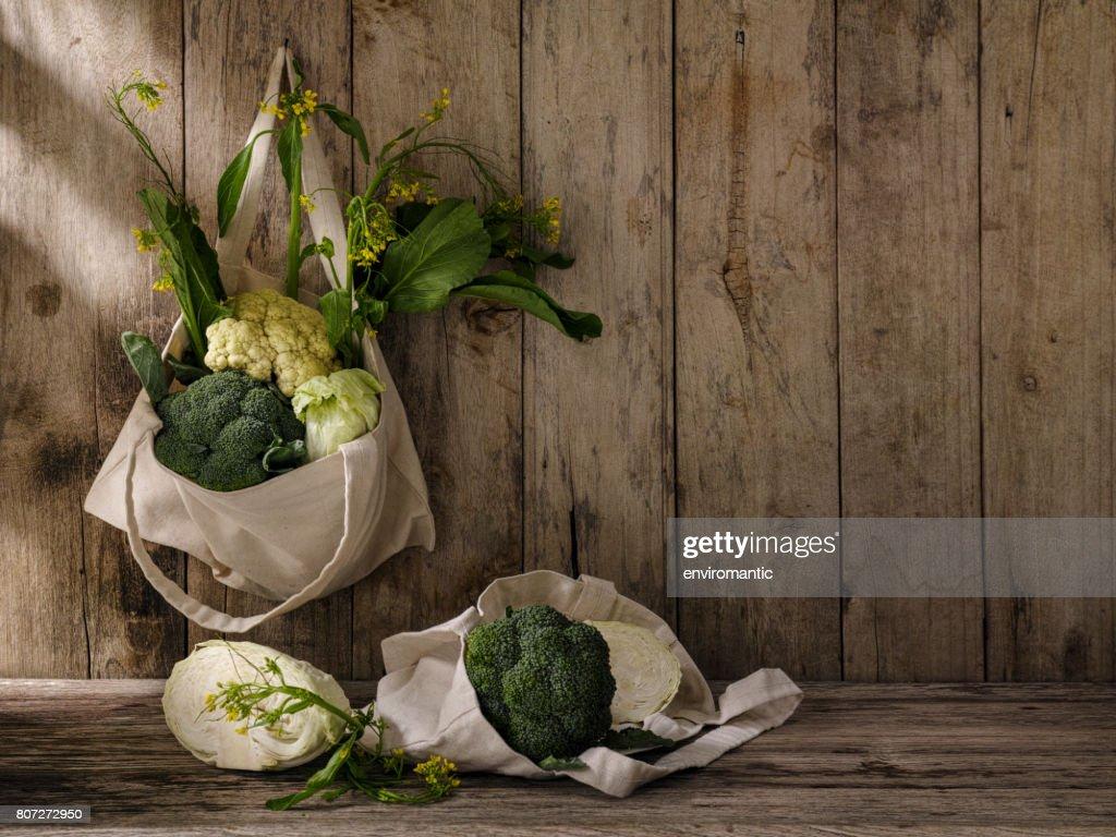 市場バッグ上の木製のテーブルの下で他の野菜との古いの風化の木製パネル壁に古いフックから掛かっている綿の再利用可能な買い物袋に新鮮な緑葉野菜。 : ストックフォト