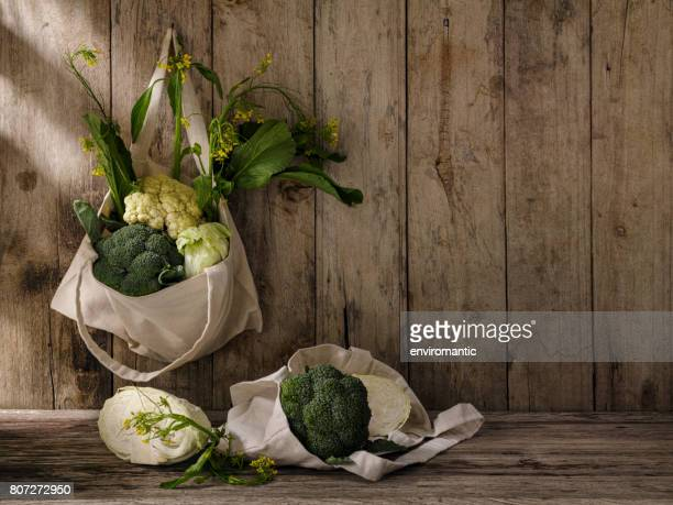 market fresh green leafy vegetables in a cotton reusable shopping bag hanging from an old hook on an old weathered wooden panel wall, with more vegetables under the bag on a wooden table. - cabbage family stock photos and pictures
