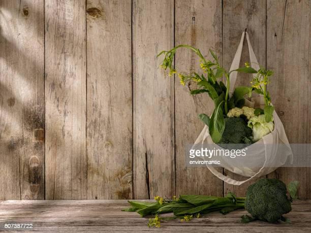 Markt frisches grünes Blattgemüse in einer Baumwolle Wiederverwendbare Einkaufstasche aus einem alten Haken hängen, eine alte verwitterte Holz Paneelwand mit mehr Gemüse unter der Tasche auf einem Holztisch.