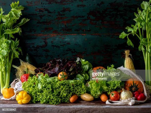 木製のターコイズ色の壁を背景に古い木製のテーブルで市場新鮮なサラダ野菜。