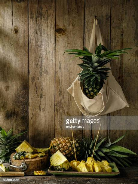 Market fresh tropical pineapple cut into chunks ready for eating on a rustic wooden table against a weathered old wooden walled background.