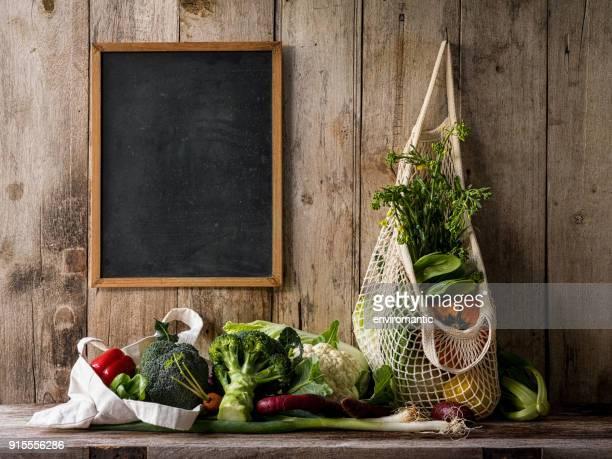 市場の新鮮な野菜が古い木の板の壁背景、他の野菜との古い木製のテーブルの上に、黒板横に再利用可能なコットン バッグにぶら下がっています。