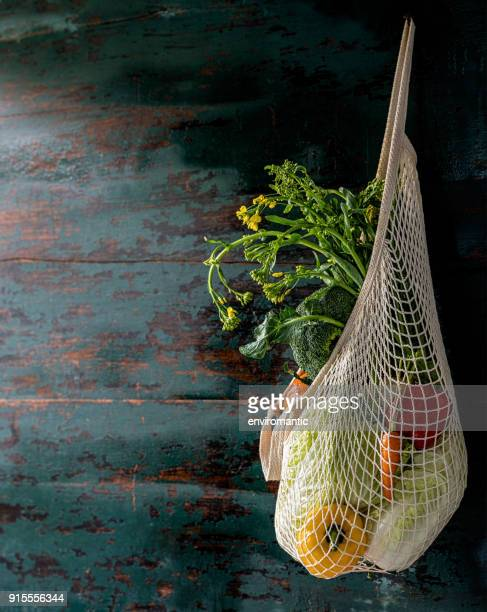Market fresh vegetables hanging in a reusable cotton string bag, on an old turquoise colored wood board wall background.