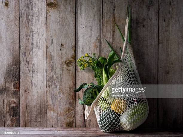 market fresh vegetables hanging in a reusable string cotton bag, on an old wood board wall background. - green stock pictures, royalty-free photos & images