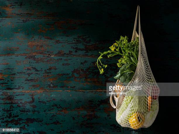 Market fresh vegetables hanging in a reusable string cotton bag, on an old turquoise colored wood board wall background.