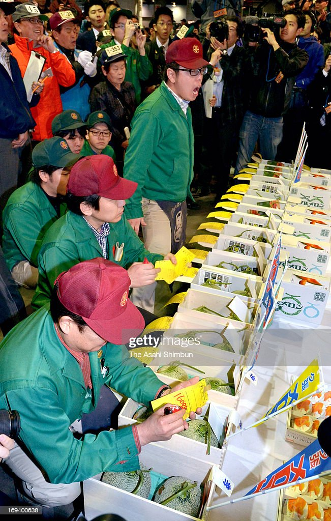 A market officer (bottom ) puts 1.6 million price tag on to the box of a pair of Yubari Melon fetched 1.6 million Japanese yen in the first auction of the season at Sapporo Central Wholesale Market on May 24, 2013 in Sapporo, Hokkaido, Japan. The highest hammer price was 2.5 million for a pair of orange-fleshed melon in 2008.