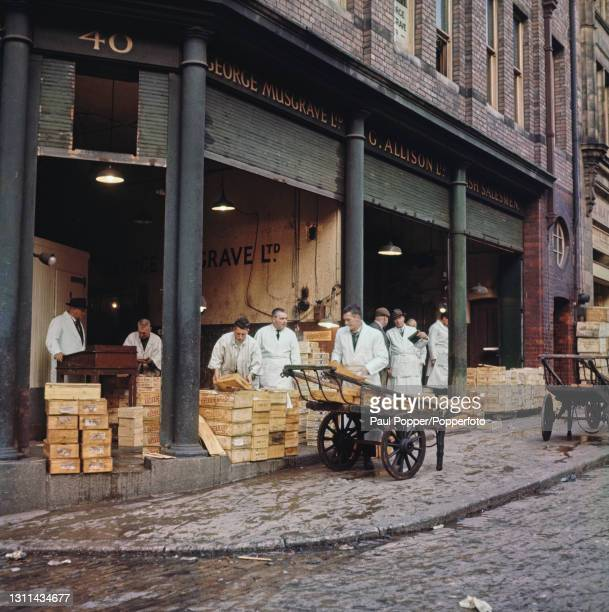 Market porter loads a barrow with boxes of fish outside a fish wholesaler's establishment on a street next to Billingsgate Fish Market in the City of...