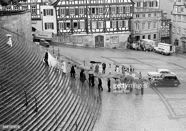 market square halftimbered houses bridal couple and wedding guests with umbrellas climb up the perron to the Saint Michael church veteran cars...