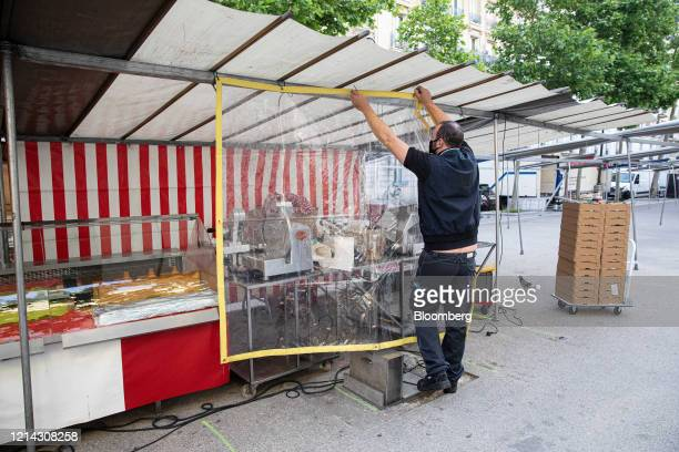 A market stall holder hangs a protective sheet over a service counter while setting up for business at Marche SaxeBreteuil in Paris France on...