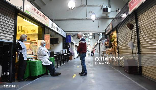 Market stall owners chat outside their stalls in Leek Market on November 11, 2020 in Leek, England. The Booksellers Association has called on the...