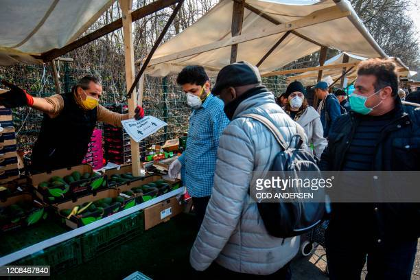 Market stall vendor tells people to keep a distance to each other at the Yorck Strasse market in Berlin on March 28, 2020 amid the novel coronavirus...