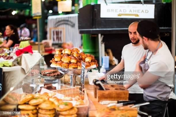 markt stall arbeitnehmer, die auf bäckerei stall im borough market, london, uk - borough market stock-fotos und bilder