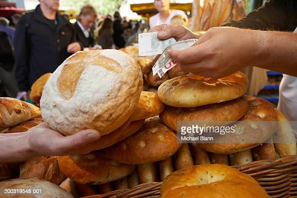 Market stallholder handing loaf to customer holding out banknotes